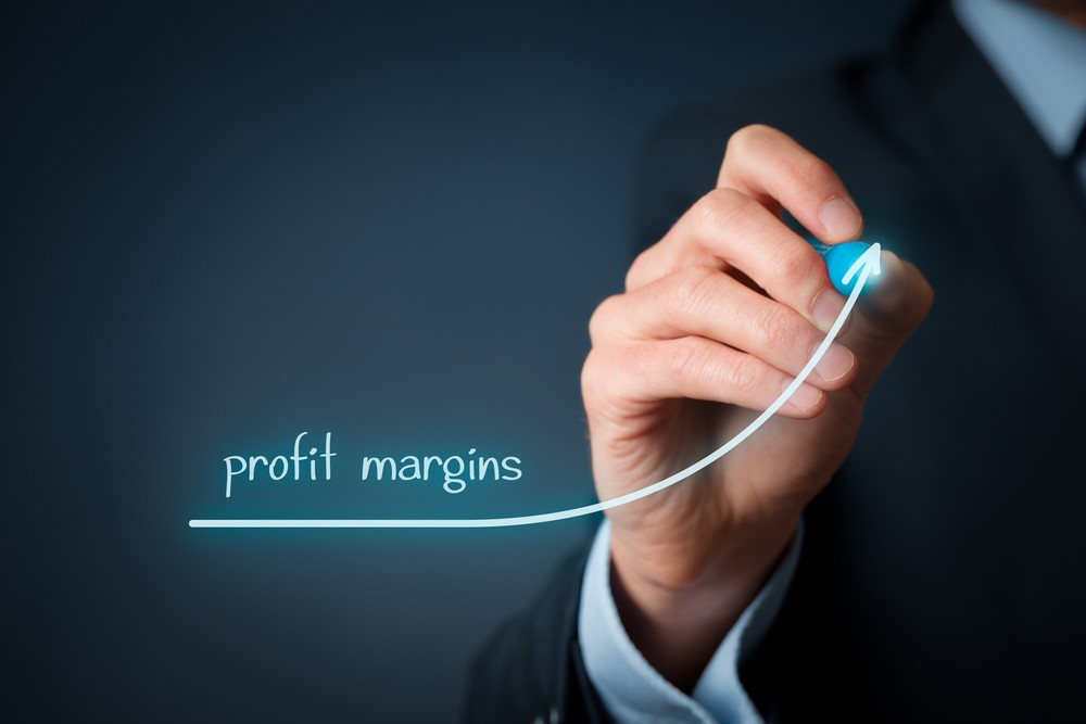 Businessman writing Profit Margins on a board represented by a Graph